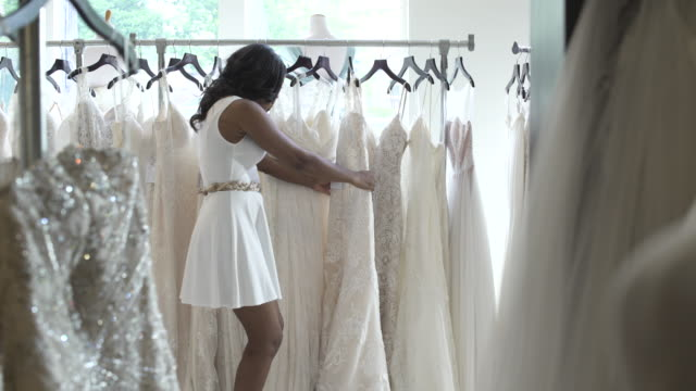 medium wide shot of a woman looking at wedding dresses - misurare video stock e b–roll