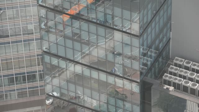 stockvideo's en b-roll-footage met medium wide shot of busy traffic reflected off windows of a skyscraper in the business district of jakarta, indonesia, medium wide shot of congested... - financieel district