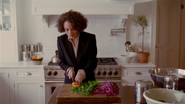 vidéos et rushes de medium woman talking on hands-free device while chopping vegetables/ solebury, pa - femme d'affaires