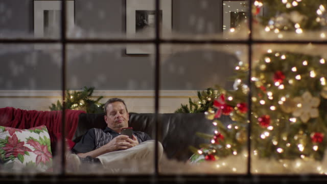 medium zoom in shot of bored man texting on cell phone on christmas / cedar hills, utah, united states - negative emotion stock videos & royalty-free footage