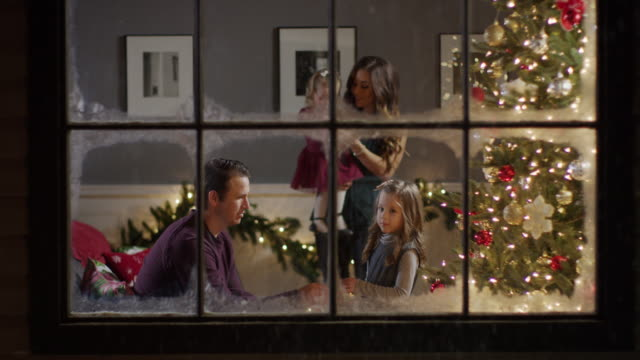 Medium zoom in shot of family decorating Christmas tree behind window / Cedar Hills, Utah, United States