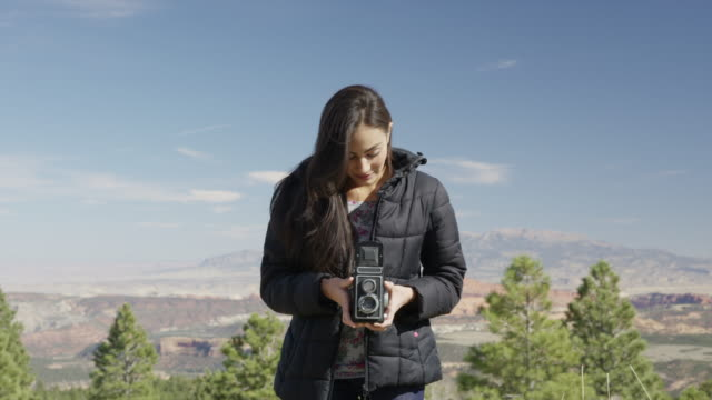 Medium zoom in shot of woman holding vintage camera in desert / Boulder, Utah, United States
