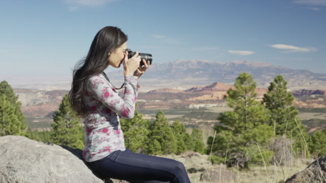 vídeos de stock e filmes b-roll de medium zoom in shot of woman photographing in desert / boulder, utah, united states - temas fotográficos