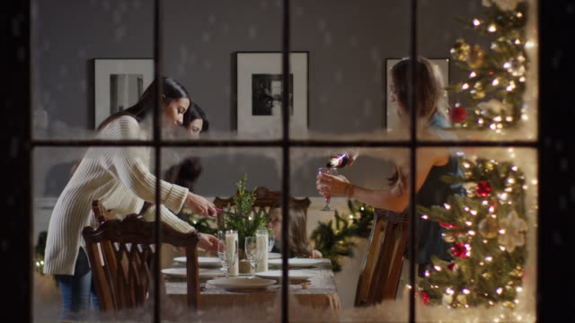 vídeos de stock, filmes e b-roll de medium zoom in shot of women setting the table on christmas behind window / cedar hills, utah, united states - forma da água