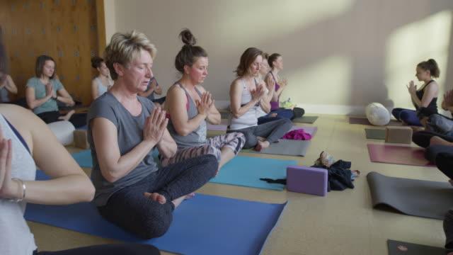 medium zoom in shot of yoga class in prayer pose / provo, utah, united states - nackenrolle kopfkissen stock-videos und b-roll-filmmaterial