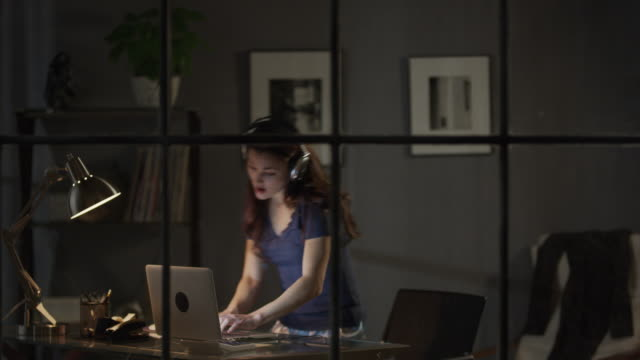 Medium zoom out shot of woman dancing to music on laptop / Cedar Hills, Utah, United States