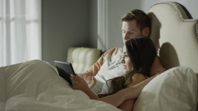 Medium zooming shot of couple using digital tablet in bed / Cedar Hills, Utah, United States
