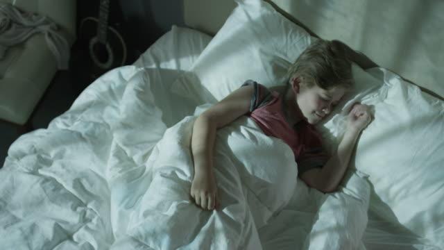 Medium zooming time lapse shot of boy sleeping in bed / Cedar Hills, Utah, United States