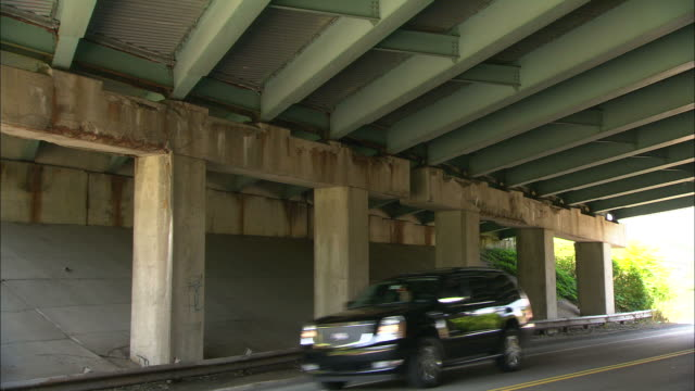 medium zoom-in-vehicles drive under a highway overpass. / usa - verletzung stock-videos und b-roll-filmmaterial