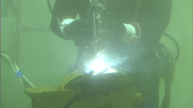 Medium zoom-out - A welder in scuba gear works underwater. / South Carolina, USA