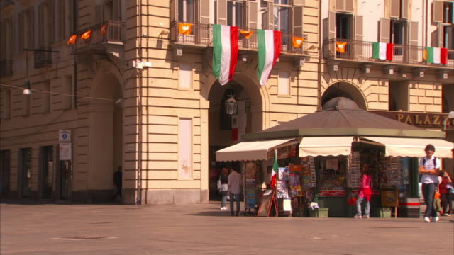 medium_static - pedestrians walk past a newsstand in a plaza in italy. / italy - bandiera nazionale video stock e b–roll