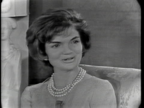 mediumclose shot of jacqueline kennedy as she sits in a chair she has short hair and is wearing a pearl necklace as well as a microphone that is... - united states and (politics or government) stock videos & royalty-free footage