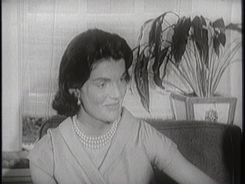 medium-close shot of jacqueline kennedy looking to her left. she is wearing strings of pearls and sitting on a cushioned seat with a potted plant... - jackie kennedy stock videos & royalty-free footage