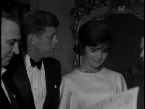 medium-close shot of john f. kennedy emerging from a car, wearing a tuxedo. he is smiling. jacqueline then emerges from the car after him, wearing a... - dinner jacket stock videos & royalty-free footage