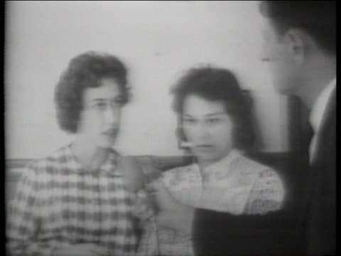 medium-close shot of two women standing next to each other, with a reporter on the right of the frame holding a microphone to them. the woman on the... - jackie kennedy stock videos & royalty-free footage