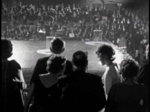 medium-close tracking shot of john f. kennedy and jackie kennedy walking right past the camera at a black-tie event. jfk is wearing a tuxedo and... - jackie kennedy stock videos & royalty-free footage
