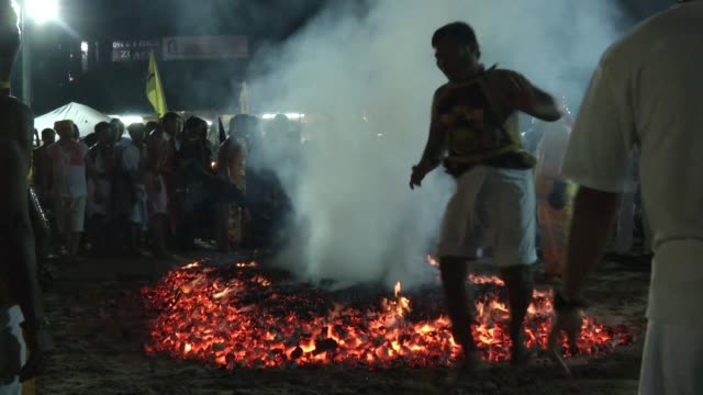 Mediums and devotees walk on burning coals during the Phuket Vegetarian Festival in Phuket Thailand