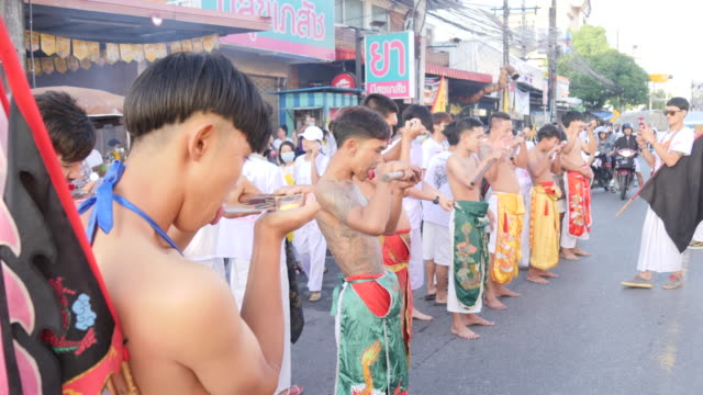 mediums or ma song, in a trance, get piercings and walk in a procession from the lim hu tai su shrine during the phuket vegetarian festival. - axe stock videos & royalty-free footage