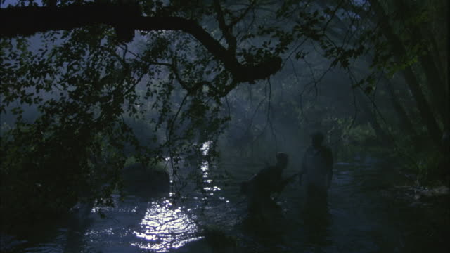 vídeos de stock, filmes e b-roll de medium-shot at night of soldiers crossing a river within a forest. - vadear