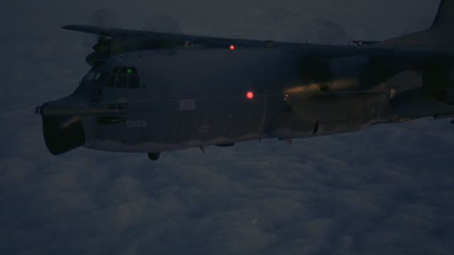medium-shot of a c-130 hercules airplane flying over a layer of clouds and descending quickly. - air vehicle stock videos & royalty-free footage