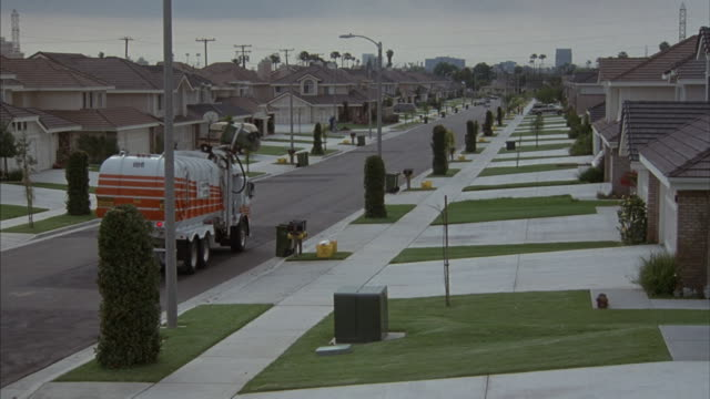 medium-shot of a garbage truck picking up trash in a manicured hawthorne neighborhood. - tract housing stock videos & royalty-free footage