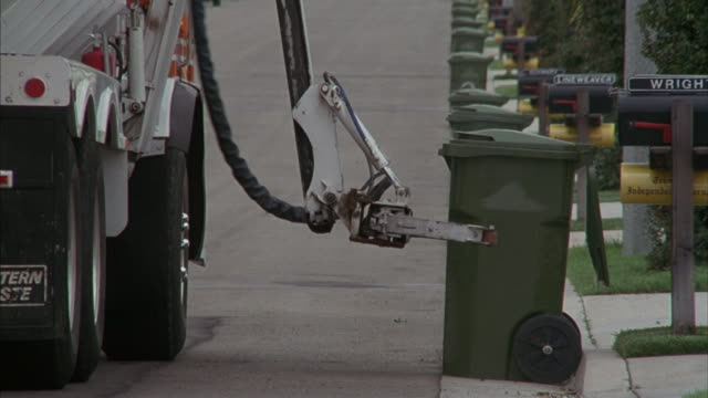 Medium-shot of a garbage truck's mechanical arm picking up and dumping a trash container.