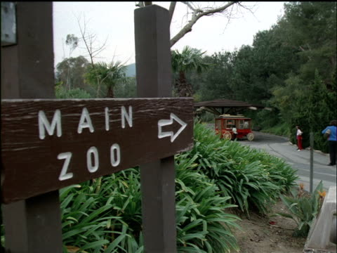 vidéos et rushes de medium-shot of a main zoo sign with a popcorn wagon and people strolling in the background. - sign