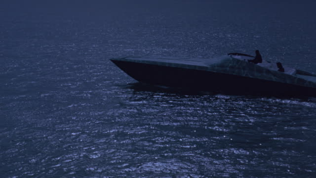 vídeos de stock, filmes e b-roll de medium-shot of a motor-boat with two silhouetted figures aboard gliding over moonlit water. - smuggling