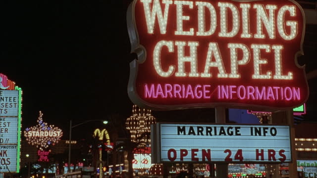 medium-shot of a nighttime wedding chapel with flashing neon lights in the distance. - chapel stock videos & royalty-free footage