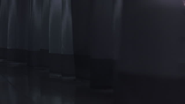 medium-shot of a person's tennis shoes as they walk through a sheer full length curtain. - mystery video stock e b–roll