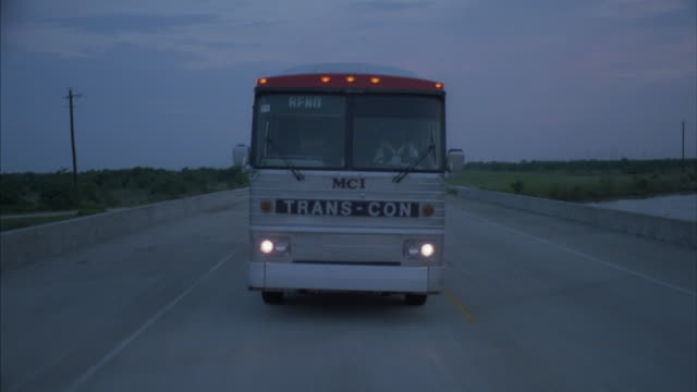medium-shot of a tour bus traveling along a country-road. - tour bus stock videos and b-roll footage