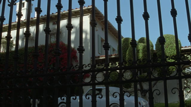 Medium-shot of a wrought iron fence with an armed bodyguard patrolling the courtyard within.