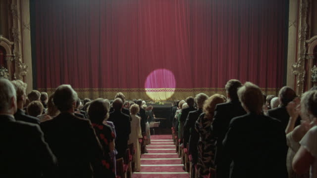 Medium-shot of an audience giving a standing ovation with a spotlight on a velvet theater curtain.
