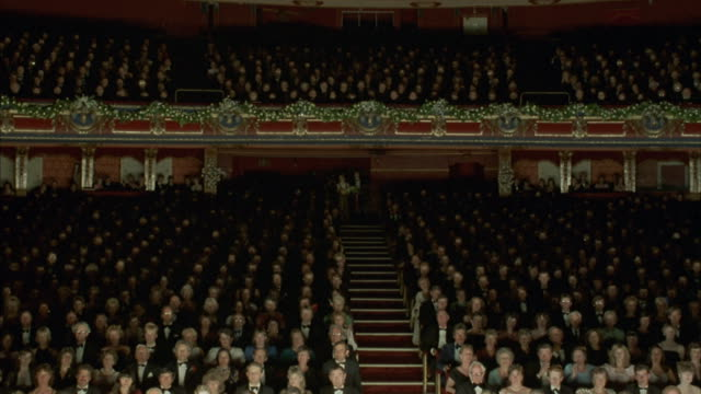 stockvideo's en b-roll-footage met medium-shot of an enthusiastic audience giving a standing ovation. - theater