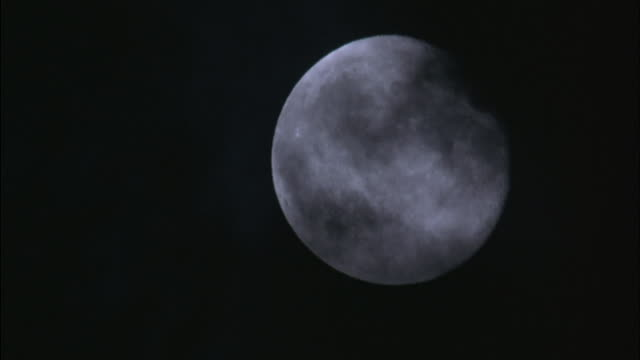 medium-shot of clouds moving across the face of the moon. - fortune telling stock videos and b-roll footage