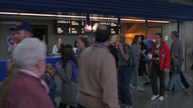 medium-shot of crowds at a football game passing a concession stand. - concession stand stock videos and b-roll footage