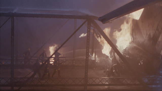 Medium-shot of firefighters trying to put out a fire on wreckage.