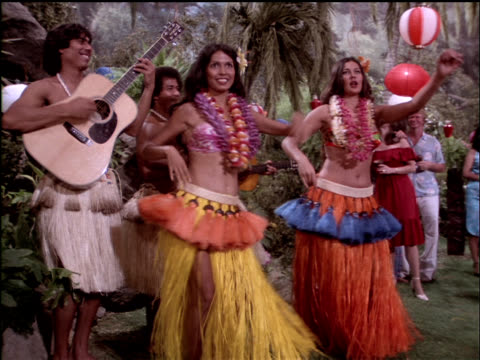 Medium-shot of hula dancers performing at a luau.