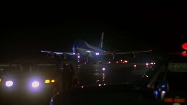 Medium-shot of lit runway at night with emergency and escort vehicles standing by as Air Force One descends to land.