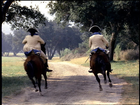 medium-shot of men in 18th century style clothing riding horses down a dirt road. - medium group of animals video stock e b–roll