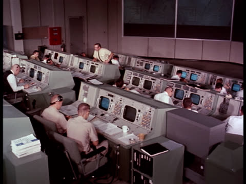 Medium-shot of NASA workers sitting at monitors in the Space Control Center.
