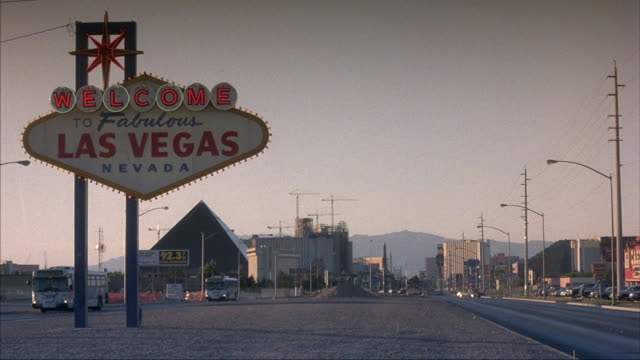 Medium-shot of the famous welcome sign to Las Vegas as a dusty breeze blows past.