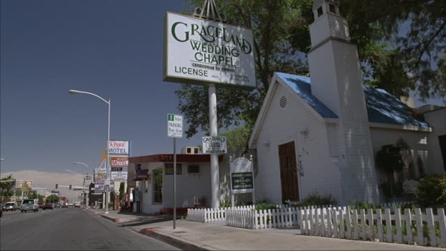 medium-shot of the tiny graceland wedding chapel in las vegas with street at left. - chapel stock videos & royalty-free footage