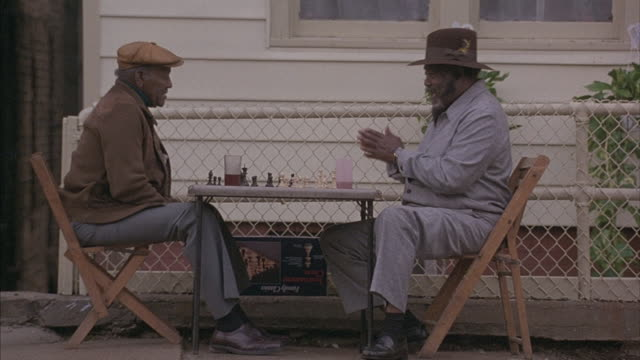 Medium-shot of two black men enjoying a chess game as a Good-Humor truck comes to a stop.