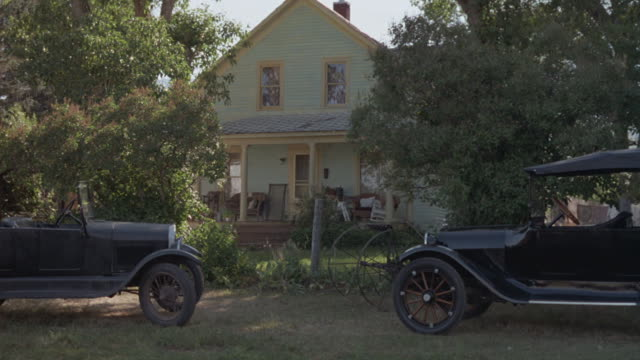 Medium-shot of two vintage Fords parked in front of a rural residential cottage.