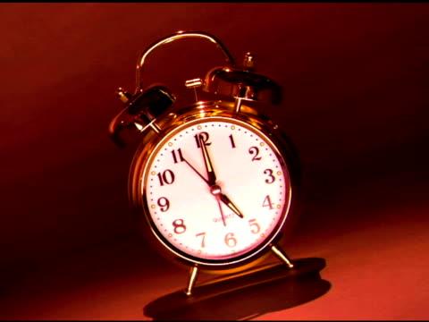 medium-wide shot of a brass alarm clock at 5:00. - brass stock videos & royalty-free footage