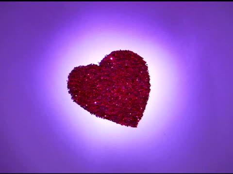 medium-wide violet toned view of a glitter heart being blown away. - tonad bild bildbanksvideor och videomaterial från bakom kulisserna