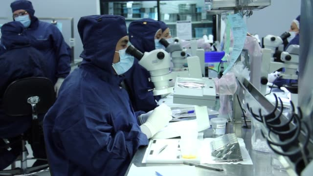 medtronic assembly plant employees walk along the assembly line at a plant in tijuana, mexico, employees use microscopes during the assembly process - plant process stock videos & royalty-free footage