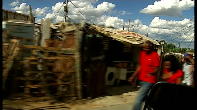 ANC meet to choose next leader SOUTH AFRICA Gauteng Johannesburg Alexandra INT CAR TRACKING SHOT people along street with huts on roadside