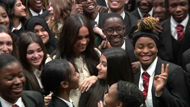 meghan duchess of sussex surrounded by schoolchildren at robert clack school of science in dagenham posing for photo for international women's day - multiracial group stock videos & royalty-free footage